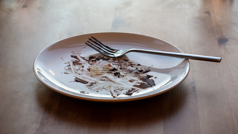 A plate with the remains of a chocolate fudge cake and a fork