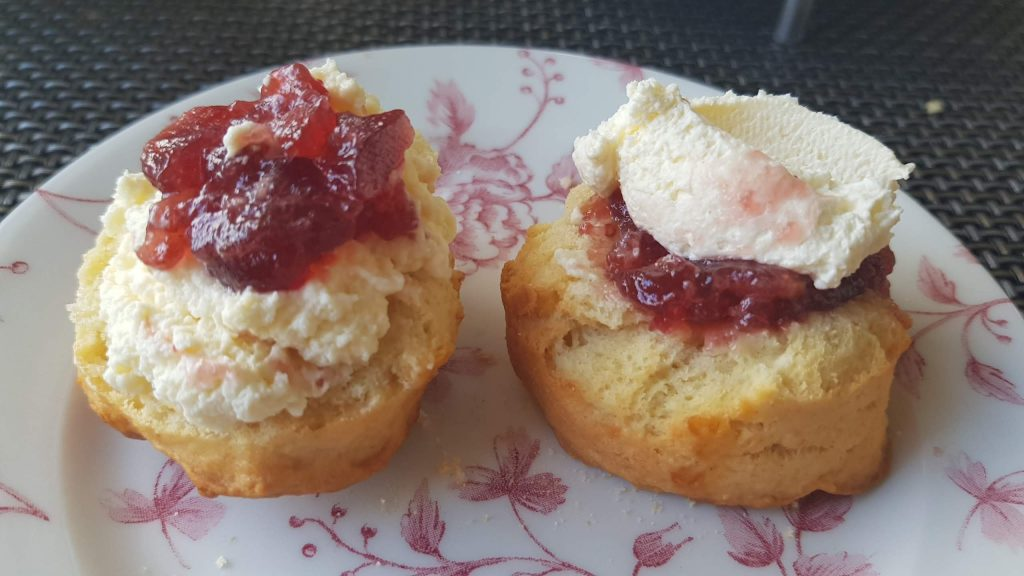 Two scone halves, one with jam then cream, the other with cream then jam.