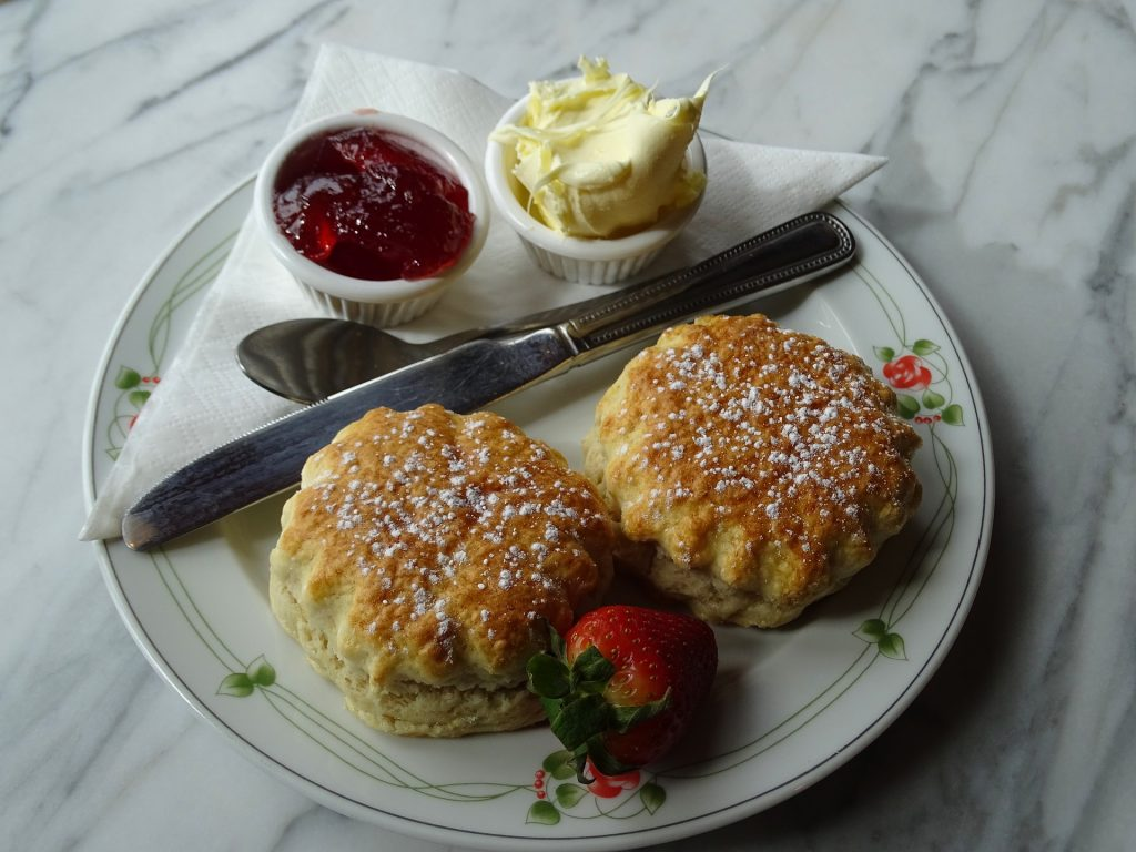 two plain scones served with pots of clotted cream and jam