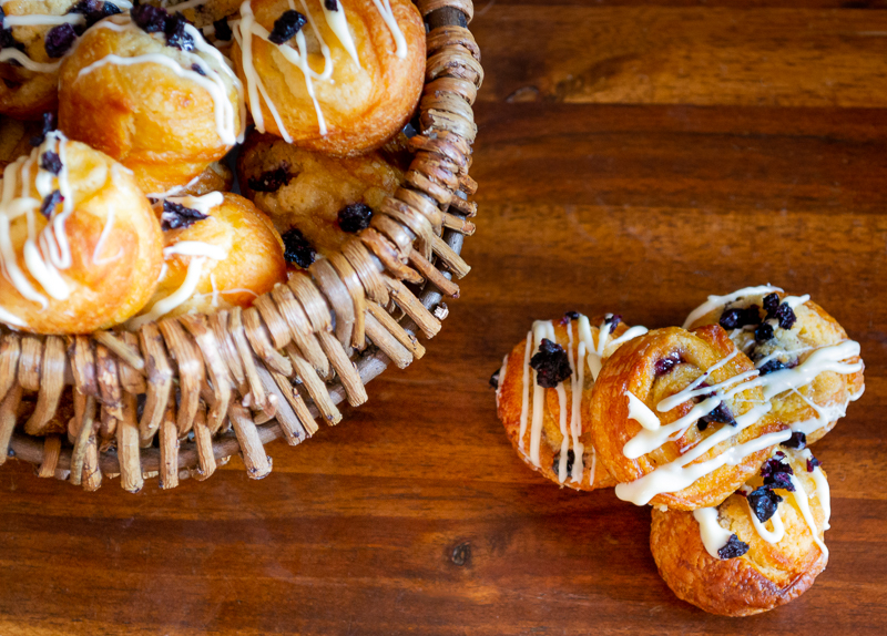 a basket of cruffins beside a stack of four. Drizzled with white chocolate.