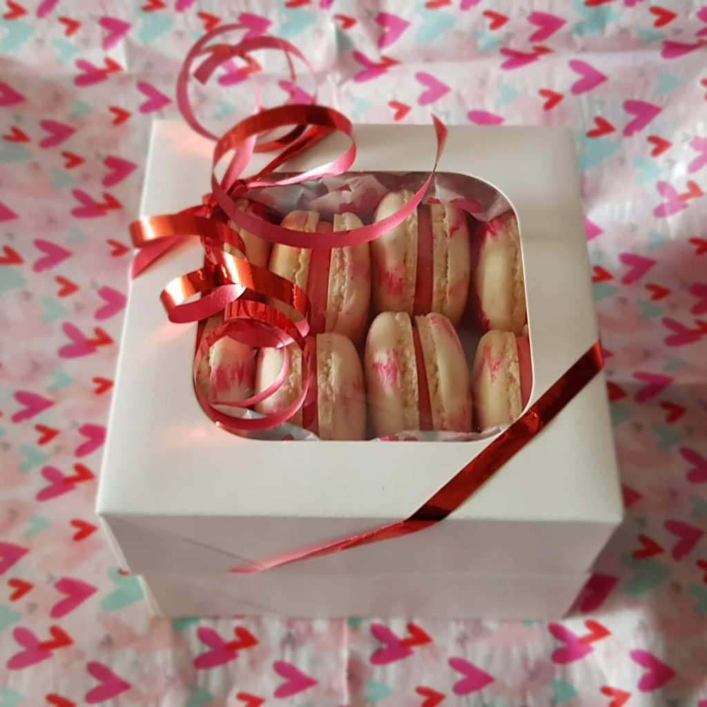 A gift box containing 8 mini red and white stripped macarons. Tied with a red ribbon.