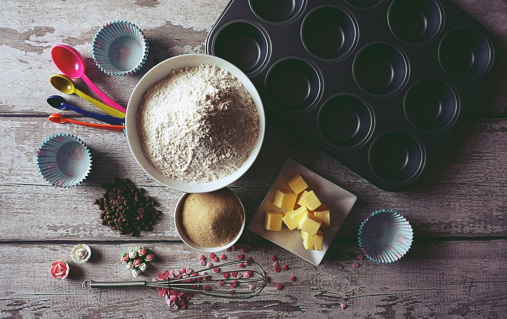 A selection of baking equipment including a cupcake tin, measuring spoons, bowls of sugar and flour, a whisk and some cubed butter.