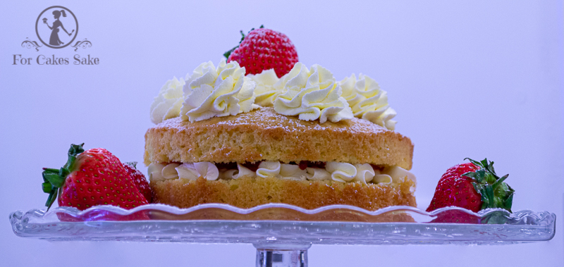 A Vcitoria Sandwich cake on a cake stand with cream and strawberries.