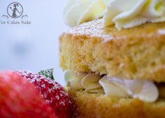 A slice of a victoria sandwich cake with fresh cream and a strawberry garnish
