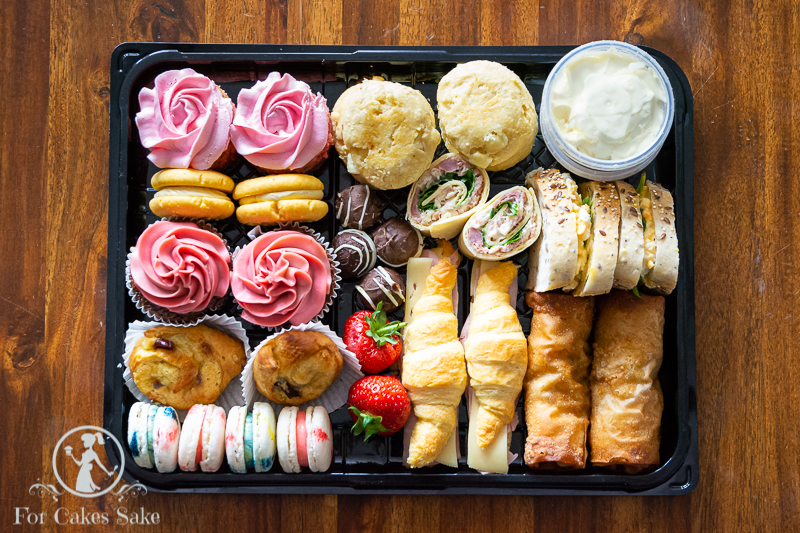 A For Cakes Sake Afternoon Tea Box. Box includes cupcakes, strawberry milkshake cake, custard shorties, cruffins, macarons, handmade chocolates, scones. It also has two sandwiches on seeded bread, two pin wheels, two mini croissants and two fajita chicken rolls. Garnished with two fresh strawberries.
