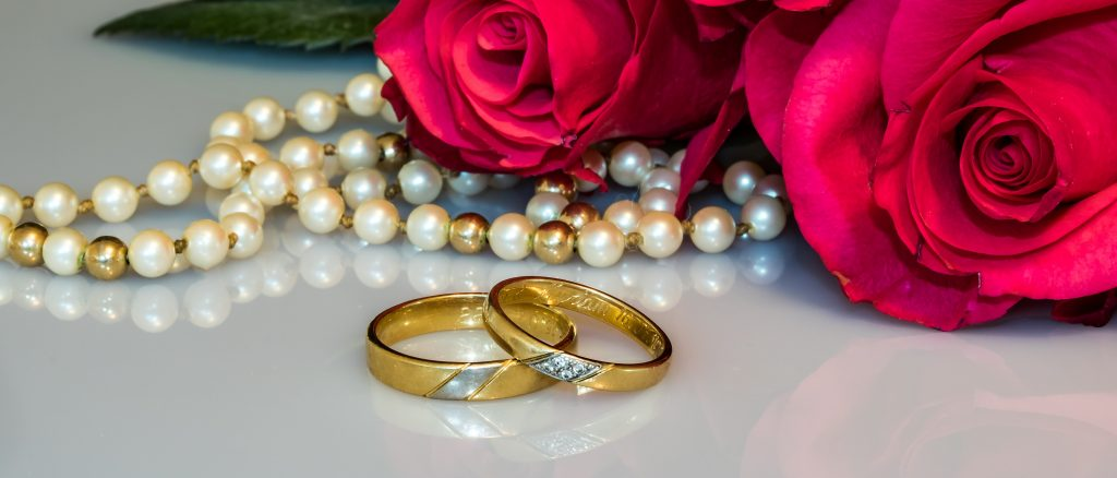 Two matching wedding rings beside red roses and a pearl necklace.