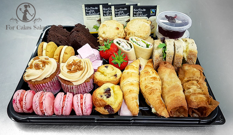 A tray with a selection of cakes, wraps, and croissants.